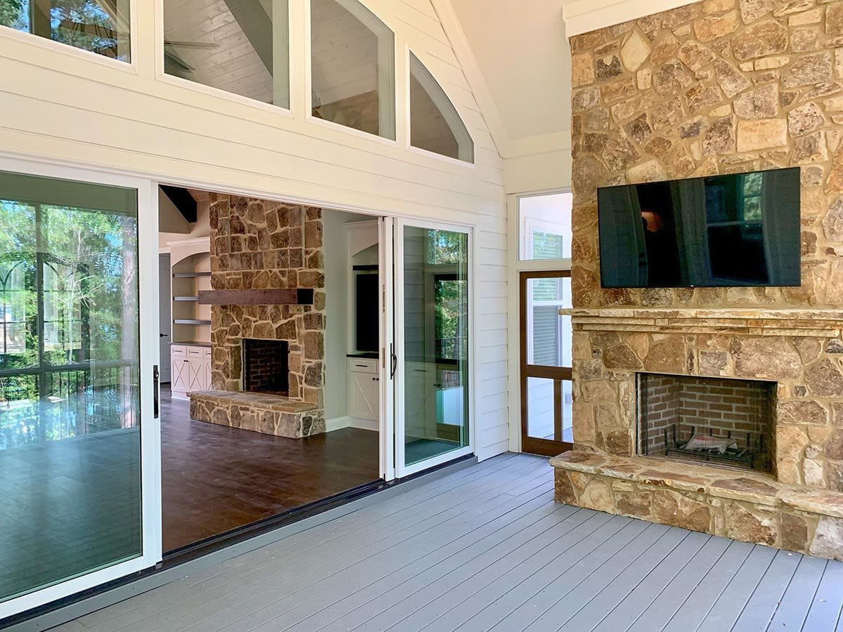 The screened porch offers a stone fireplace and a wall-mounted TV.