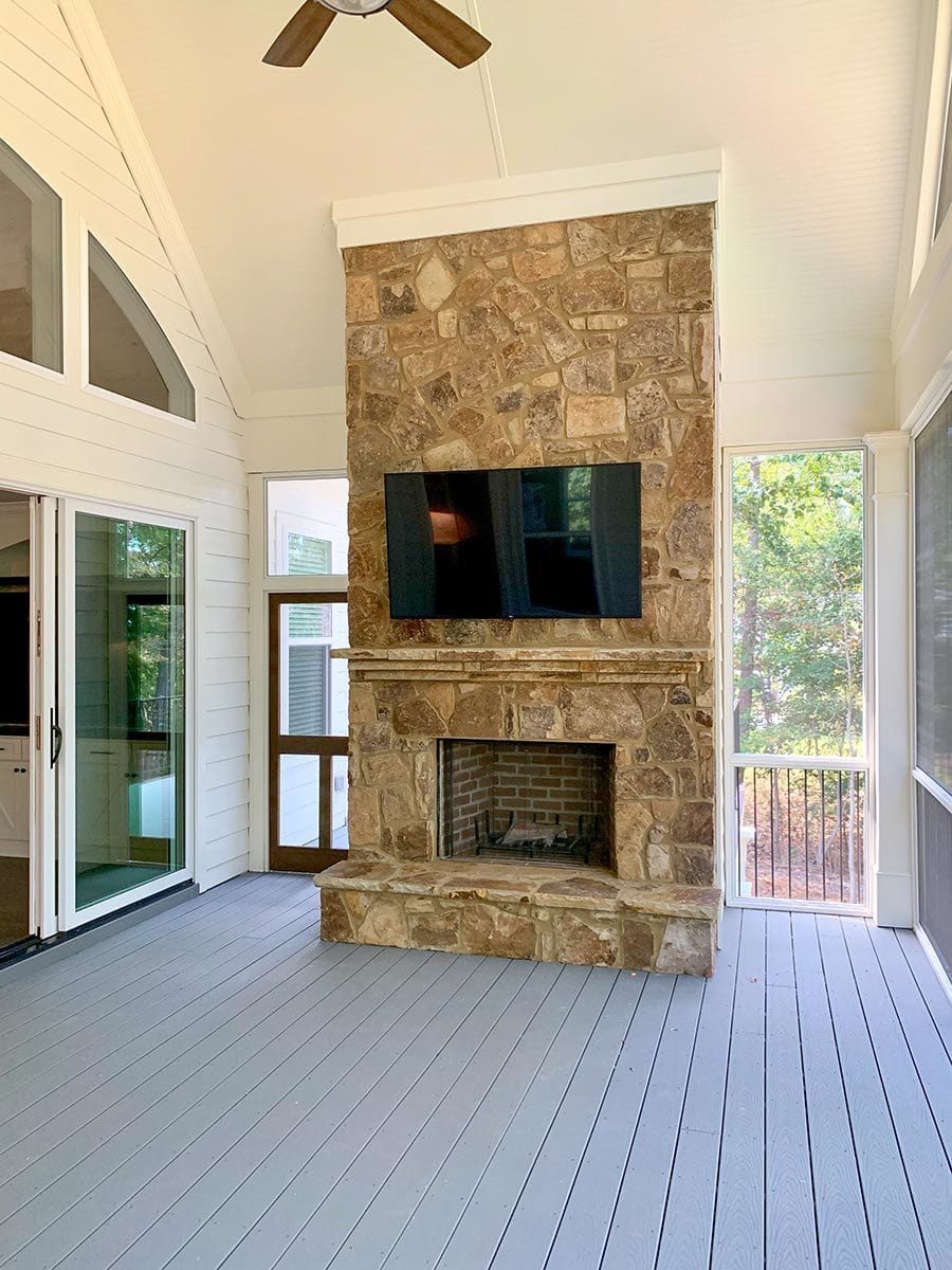 Glass windows and door flank the stone fireplace.