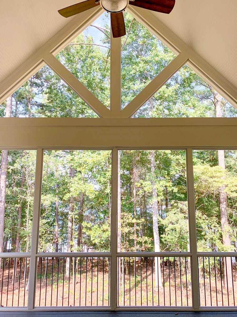 The screened porch includes a cathedral ceiling mounted with a ceiling fan.