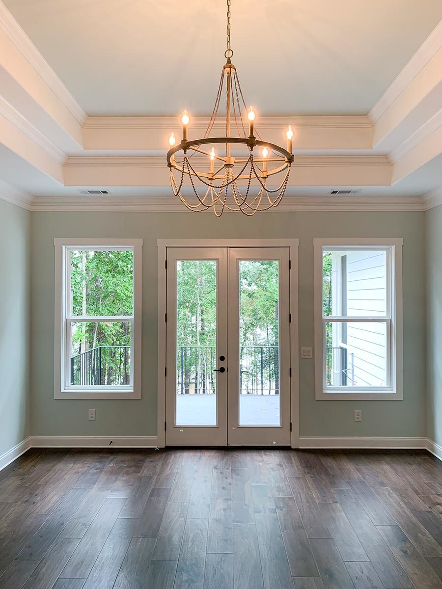 This is the primary bedroom with a stunning tray ceiling and a private deck accessible via a french door.