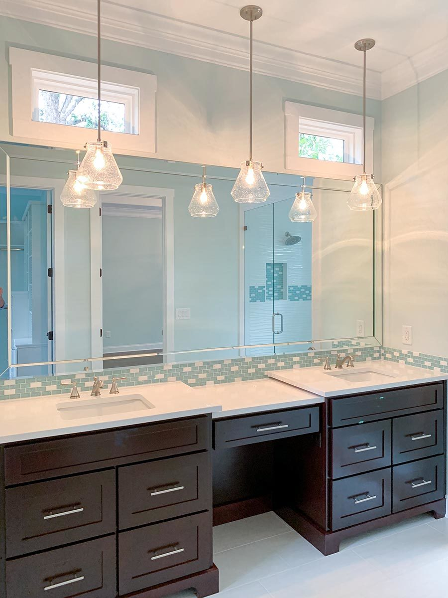 The primary bathroom features a double sink vanity paired with a large rectangular mirror and glass pendants.