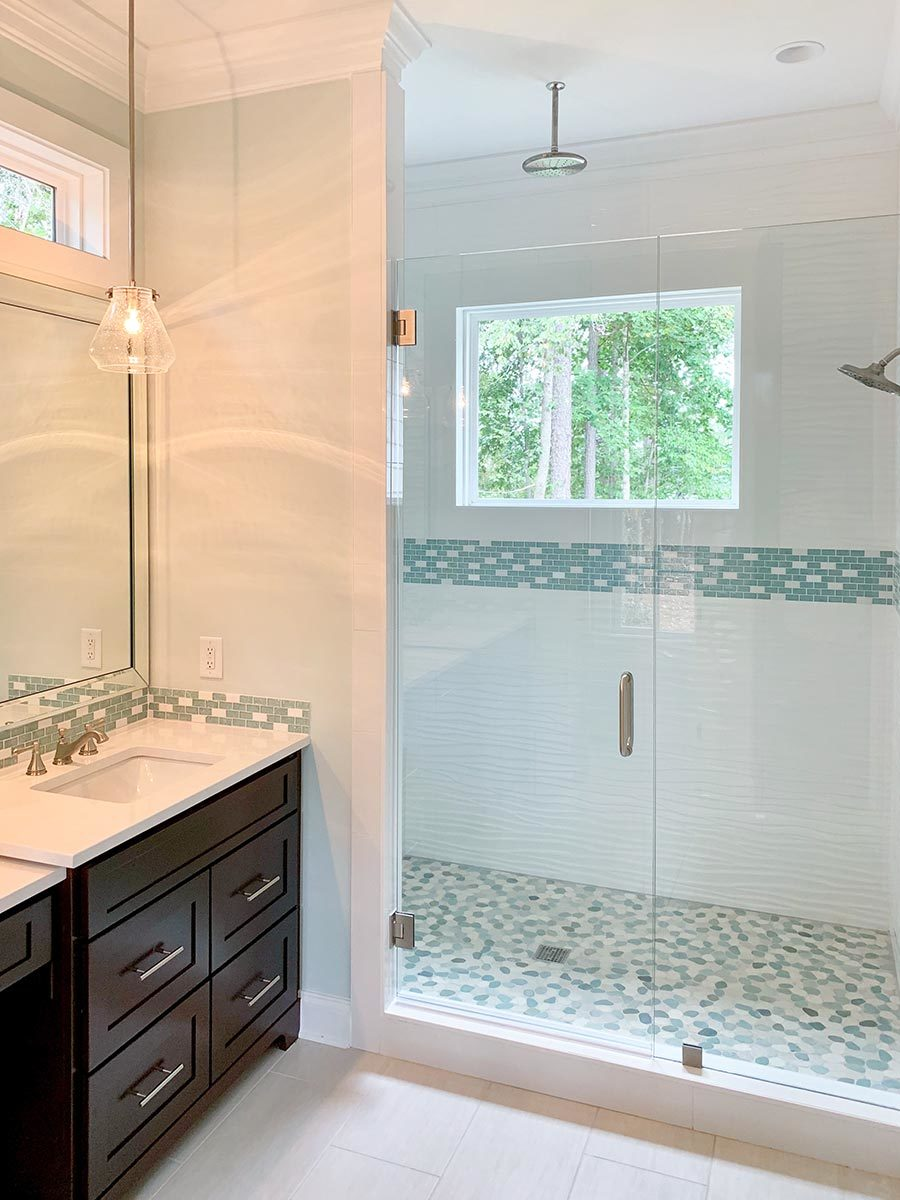 Walk-in shower with chrome fixtures, mosaic tile flooring, and a glass hinged door.