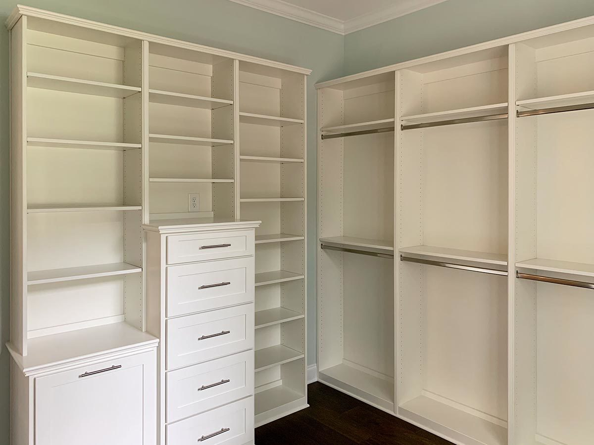 The walk-in closet has light blue walls and white built-ins.