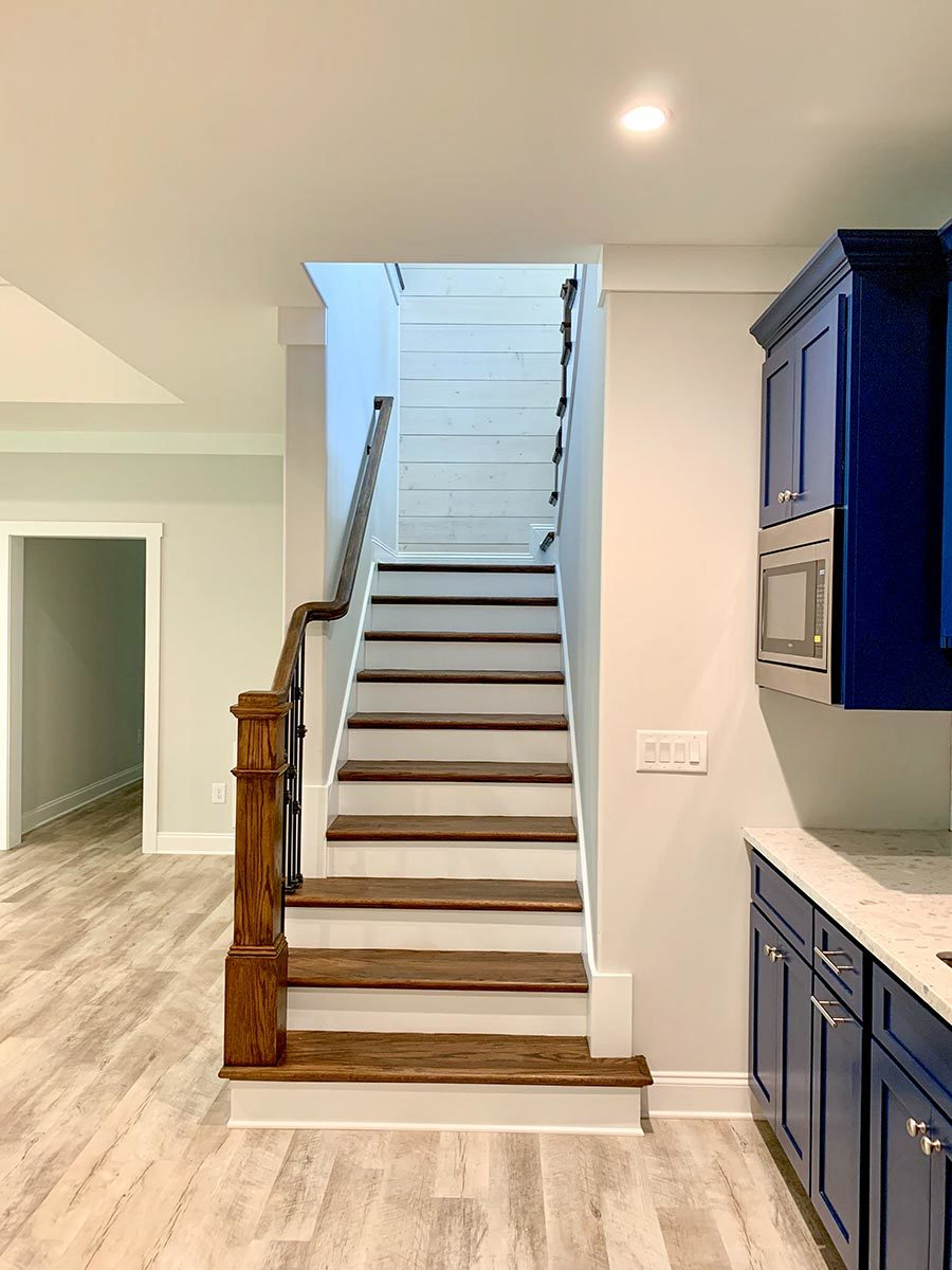 At the bottom of the stairs, you are greeted by a wet bar with blue cabinets.