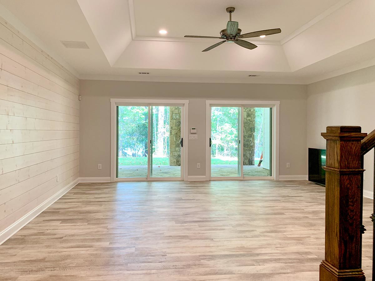 Recreation room with a tray ceiling and two sets of sliding doors leading out to the patio.