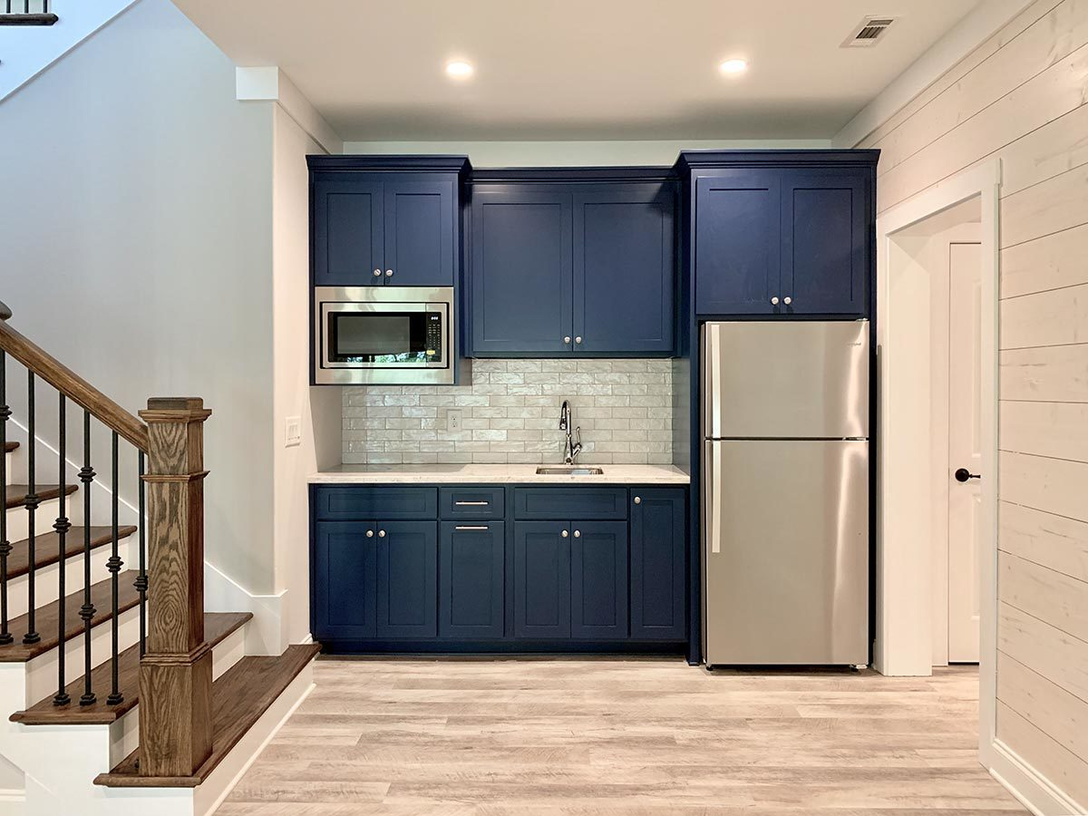 Wet bar with blue cabinets, two-door fridge, and an oven.