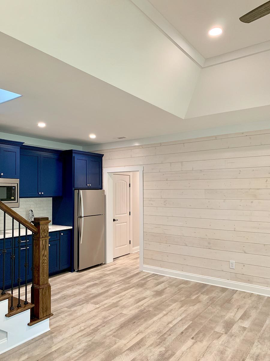 A doorway next to the wet bar opens to a hallway that leads to a bedroom and exercise room.