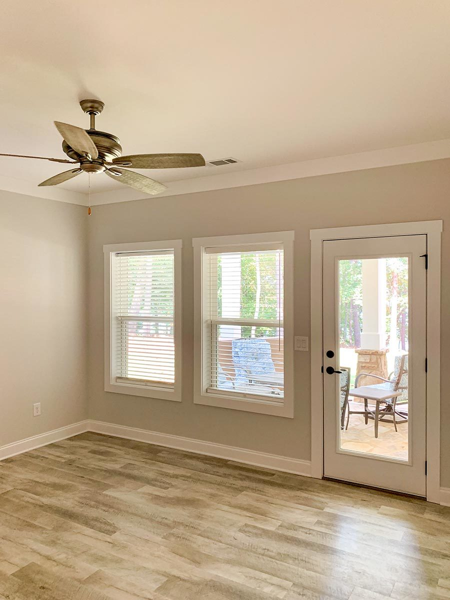 Bedroom with hardwood flooring, gray walls, and a glass door leading out to a covered patio.