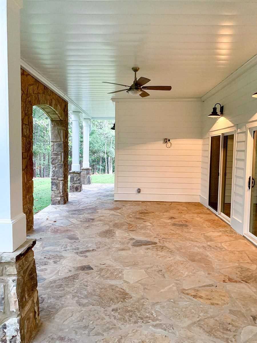 The covered patio has flagstone flooring, tapered columns, and keystone arches.