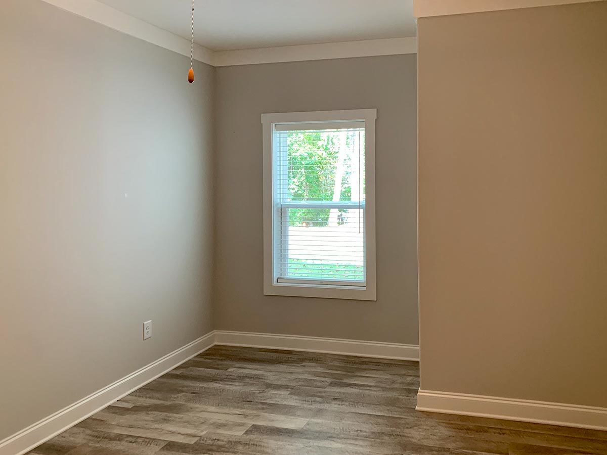 Exercise room with gray walls, hardwood flooring, and a white framed window.