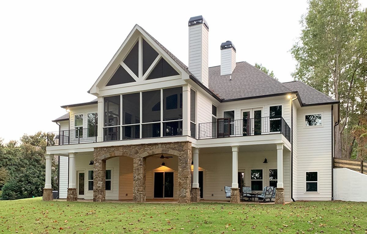 Rear exterior view showing the chimneys, white siding, and covered porch bordered by tapered columns.