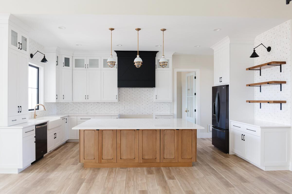 The kitchen is equipped with marble countertops, a farmhouse sink, a wooden center island, and black appliances that set stunning contrast to the white cabinetry.