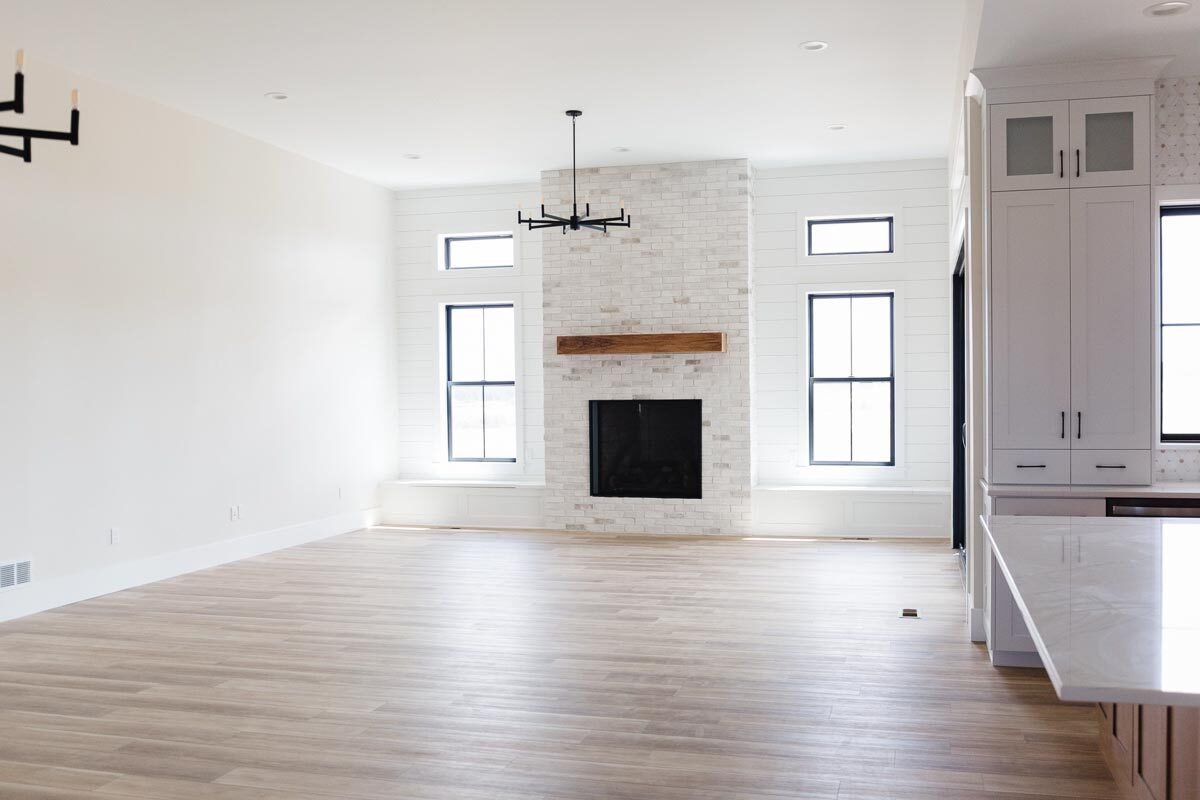 This is the living space with hardwood flooring and a fireplace.