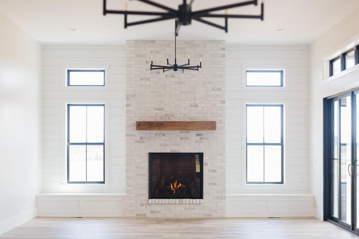 Black-aluminum framed windows flank the brick fireplace.