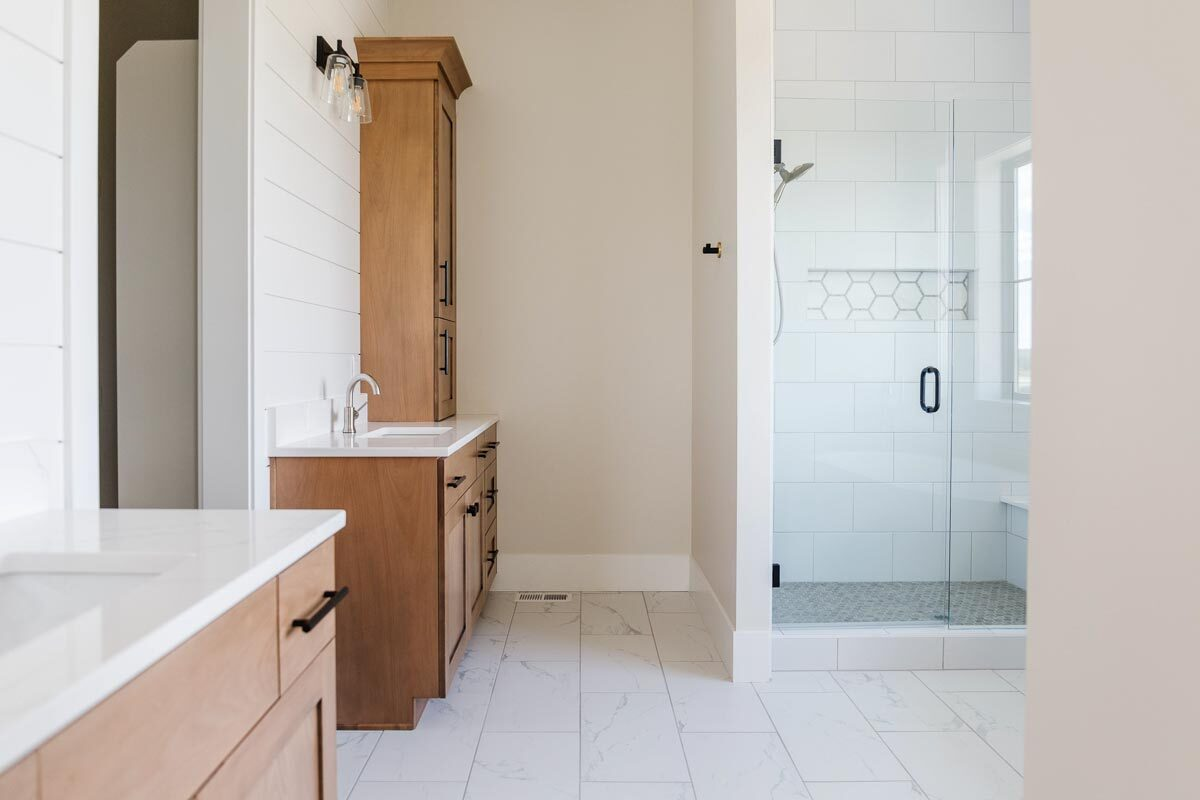 His and her sink vanities with wooden cabinets and marble countertops complete the primary bathroom.
