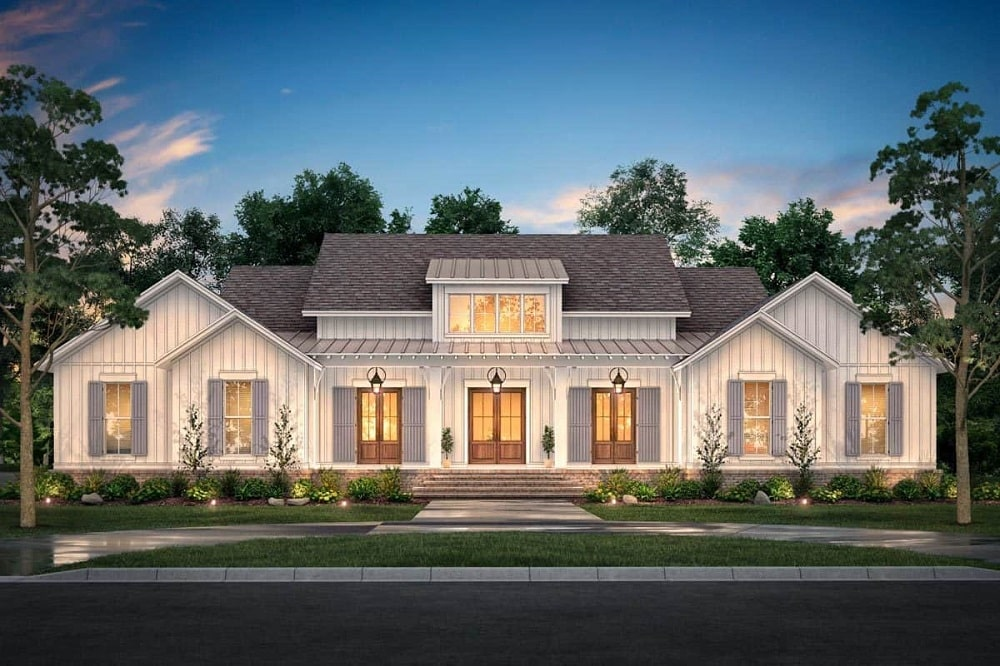 The bright beige exterior walls of this farmhouse-style home is complemented by the warm glow that comes from the interiors and escape through the windows and the three doors with glass panels at the main entrance.