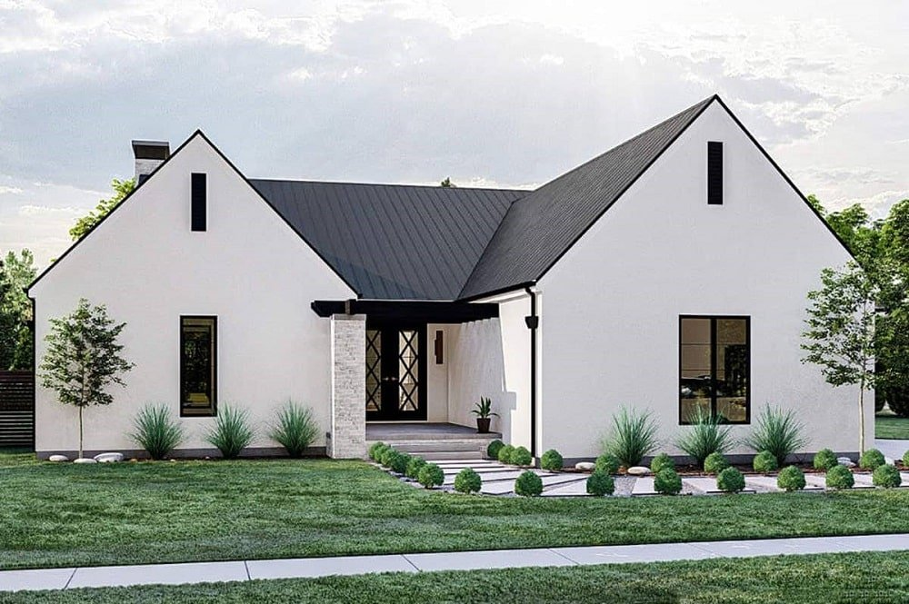 This is an ultra modern farmhouse-style home with a U-shape to it. It has a main entrance in the middle with a concrete walkway flanked by shrubs and grass lawn.
