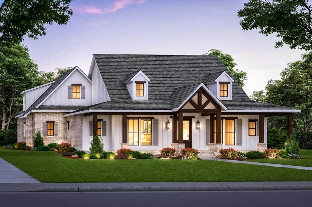 This is an exterior view of the house that has dark gray roof, dormer windows and a main entrance that is adorned with exposed wooden beams to match the pillars that stand out against the bright exterior walls.