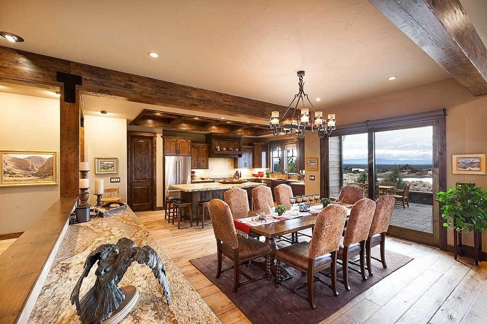 The dining room offers brown leather seats and a rectangular dining table under the ornate chandelier that hangs from the ceiling with massive exposed beams that match the frame of the glass doors.