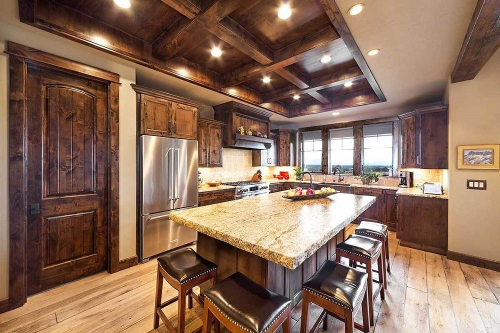 The kitchen is flooded with natural and ambient lights coming from the glazed windows and recessed lights fitted on the coffered ceiling. This matches well with the dark wooden cabinetry that makes the stainless steel appliances stand out.
