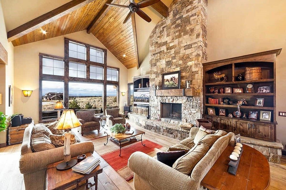 A massive window by the living room takes in an expansive view along with an ample amount of natural light. This complements the living room with its tall arched ceiling, sofa set and large stone fireplace across from the glass-top coffee table.