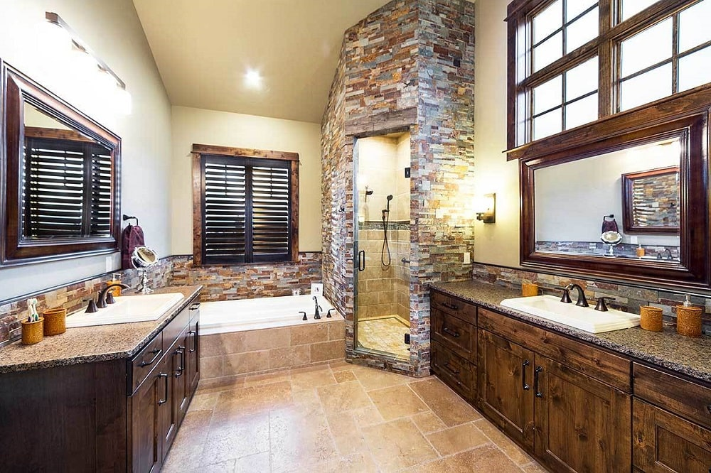 The primary bath is equipped with a deep soaking tub, a separate shower with mosaic stone walls that match the backsplash, and facing granite top vanities.