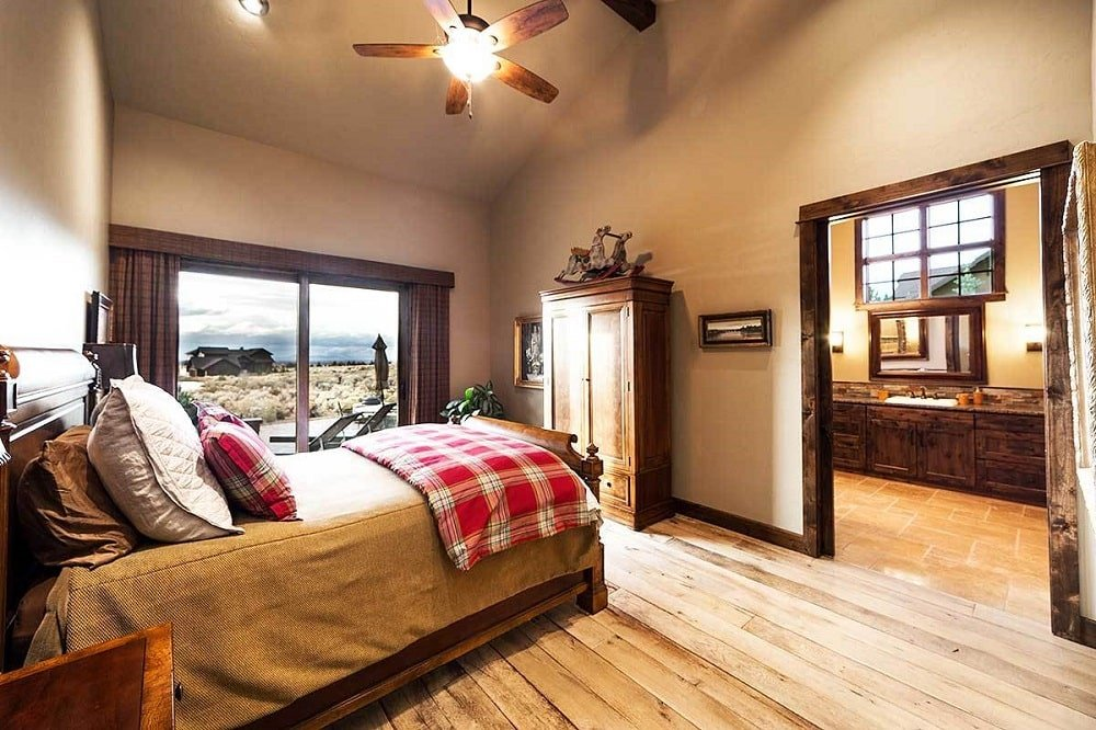 Primary bedroom with a cathedral ceiling, wide plank flooring, and glass sliders that lead to the rear patio. It has wooden features on its flooring, cabinets and frames that match the bed.