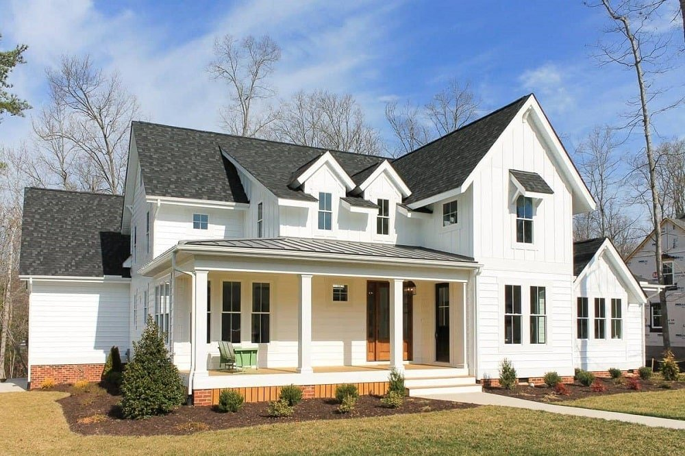 This modern farmhouse-style home has bright exteriors to contrast the dark roof that has dormer windows and a porch underneath.
