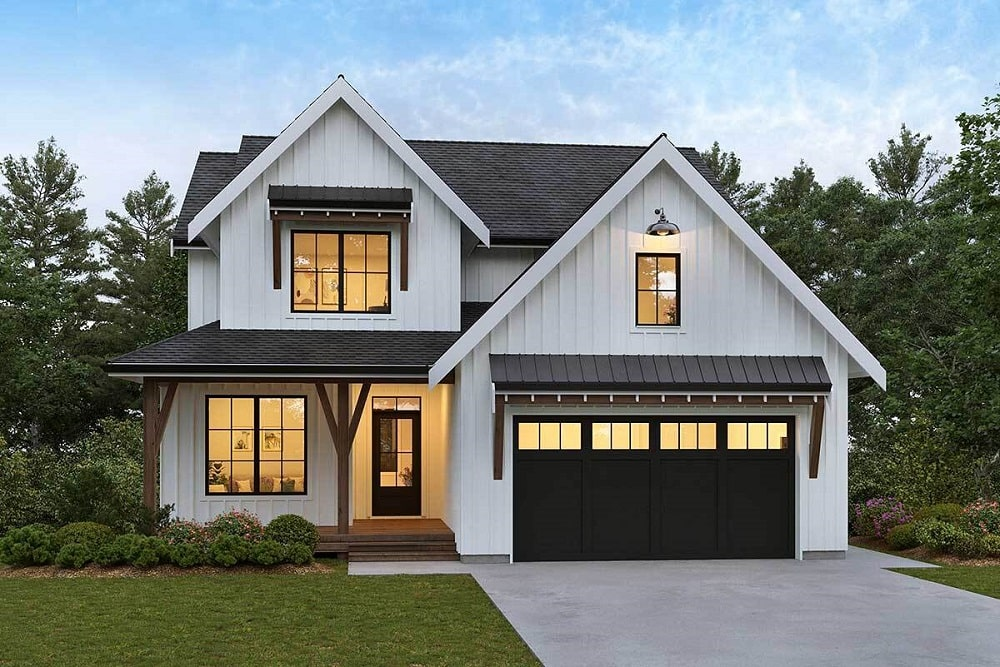 This is a two-story modern farmhouse-style home with a large dark garage door that contrasts the light tone of the exterior walls with warm glow from the windows.