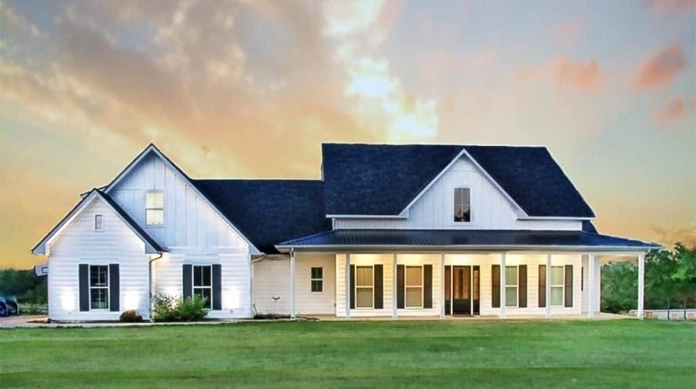 This is farmhouse-style home is surrounded grass lawns that lead to the wrap-around porch of the house topped with a cover that is supported by thin pillars that match the white exterior walls.