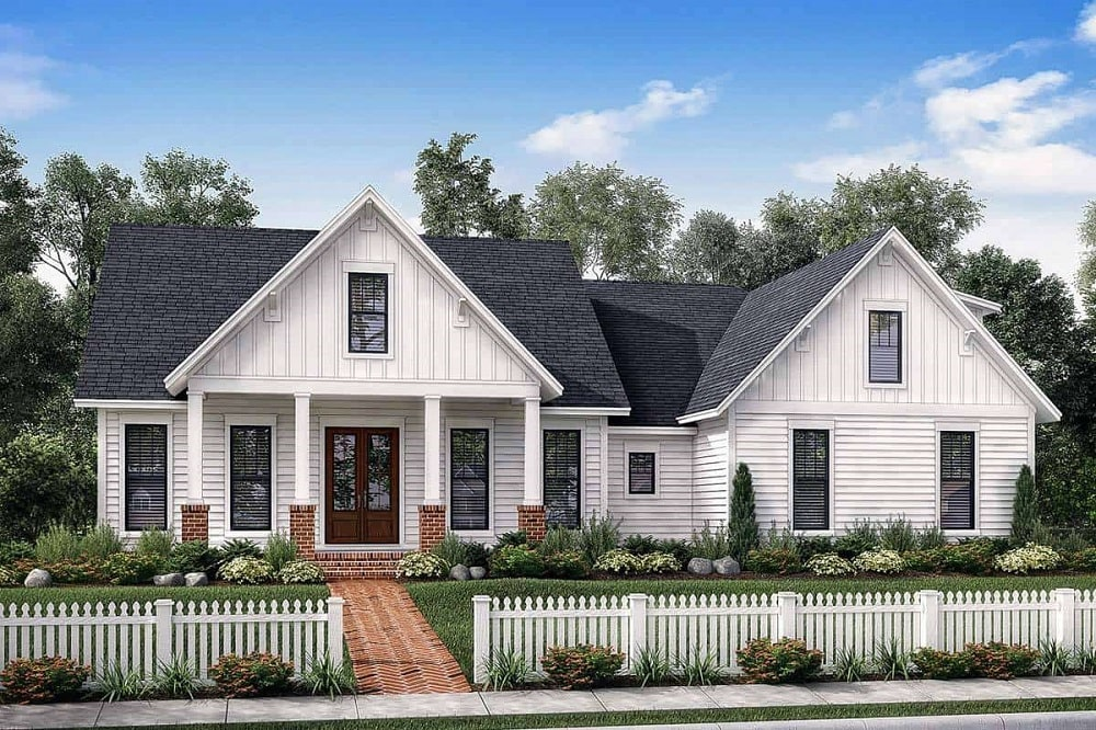 This is a front view of the farmhouse-style home with bright exterior walls complemented by a landscaping that has white picket fences, a large grass lawn and a brick walkway that leads to the covered entrance with a brown main door.