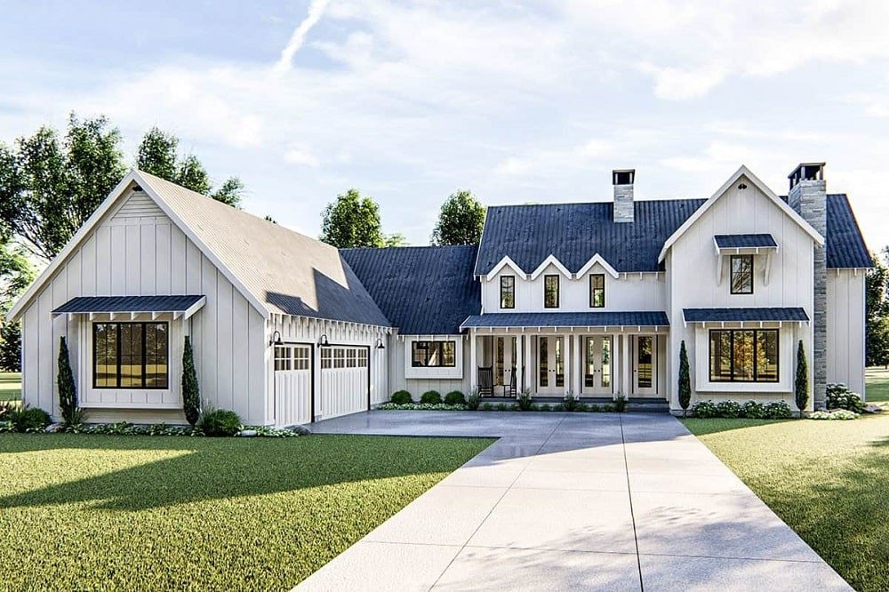 This is a front view of the farmhouse-style home with an L-shape design. You can see here the garage doors on one side and the main entrance on the other topped with dormer windows and chimneys.