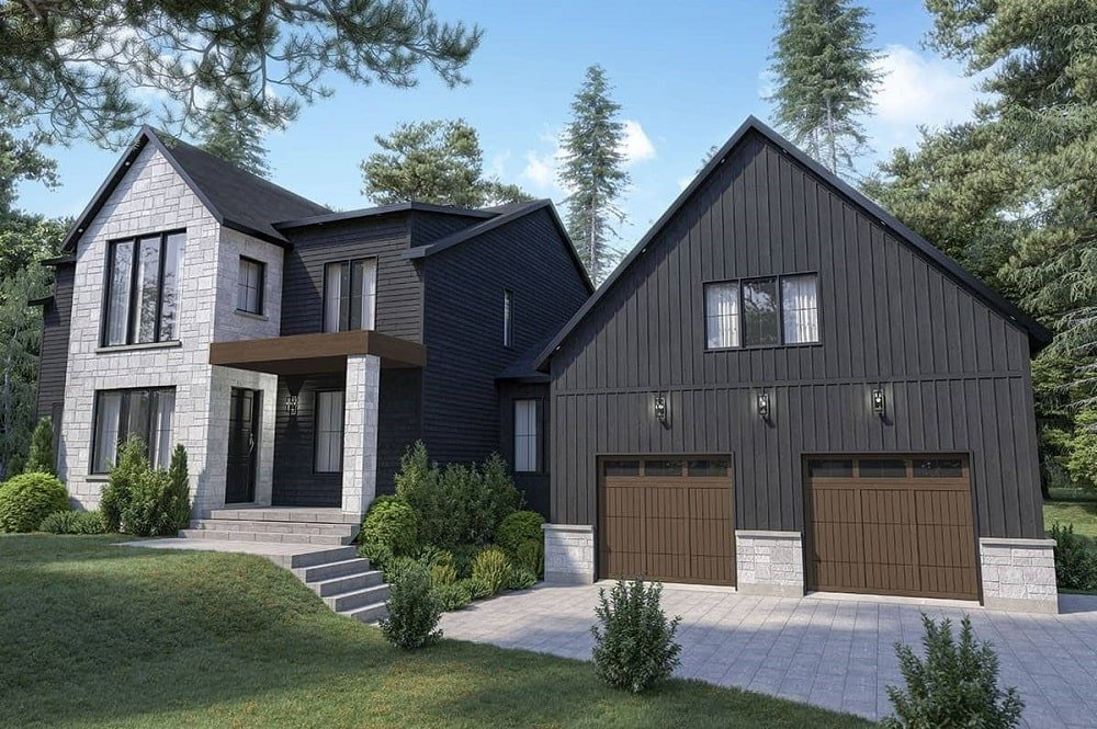 This is a front look at the exterior of this farmhouse-style home with black wooden exterior walls complemented by the light gray stone accents and the windows as well as the surrounding landscape.
