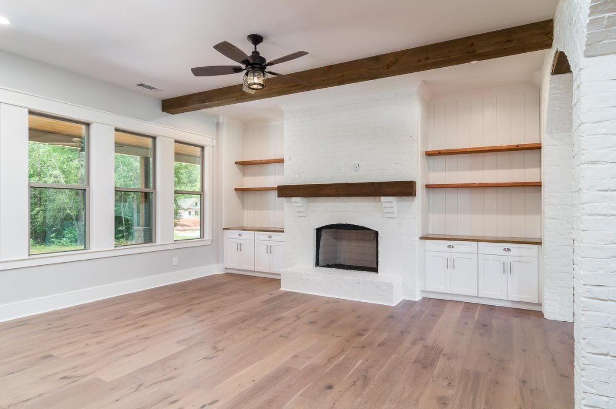 The living room offers a white brick fireplace flanked by built-in cabinets and floating shelves.