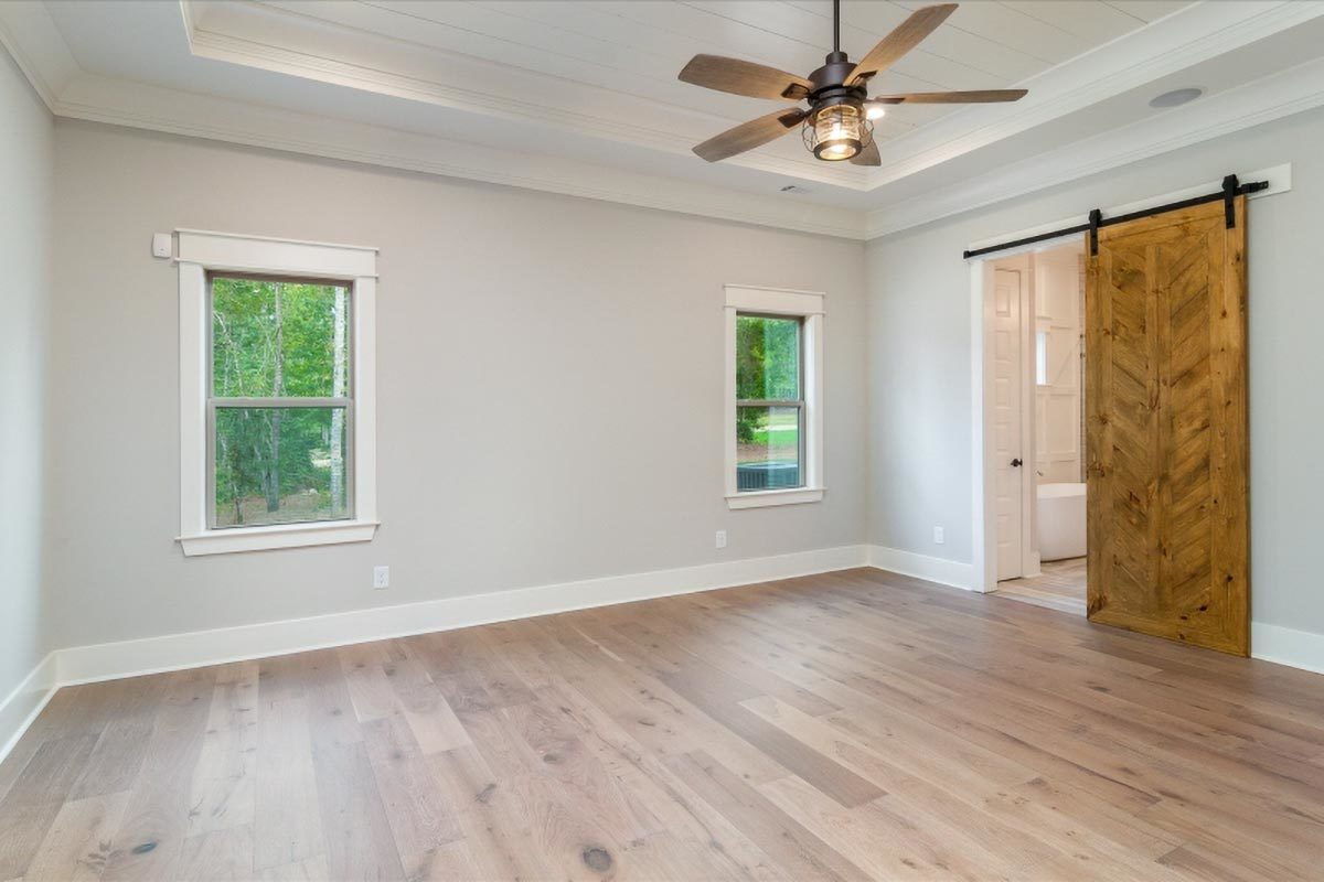 Primary suite with hardwood flooring and an elegant tray ceiling. A barn door on the right side reveals the primary bath.