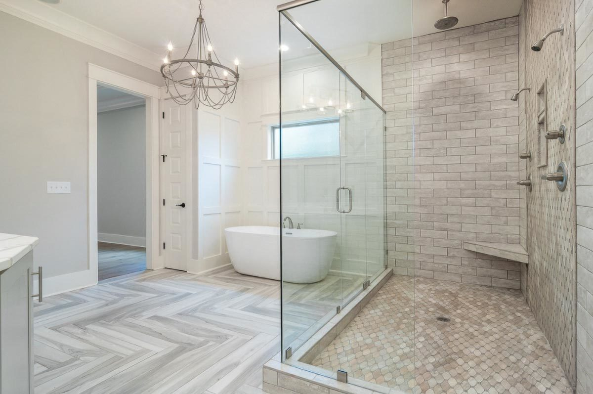 Primary bathroom with a marble top vanity, a freestanding tub, and a spacious walk-in shower.