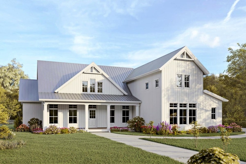 This is a two-story modern farmhouse-style home with light beige wooden exterior walls complemented by the multiple windows and the colorful landscaping of shrubs and grass lawns.
