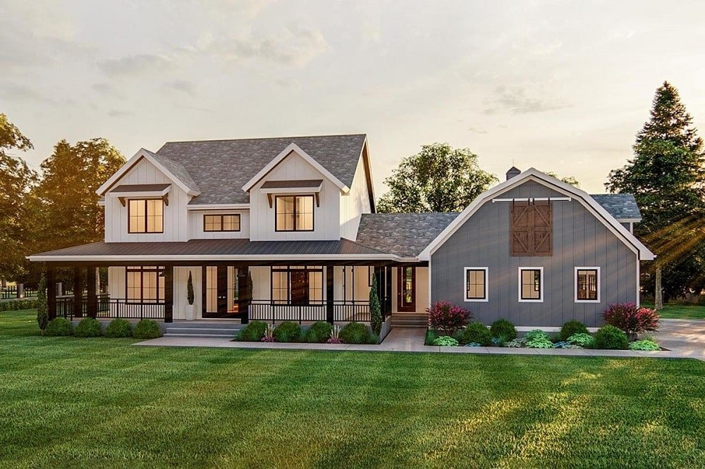 This is a look at the front of the house that has a wrap-around porch and a side load barn-style garage. with a gray tone to its exterior walls.