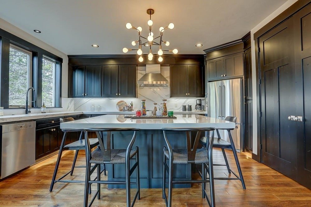 This is a close look at the kitchen with dark wooden cabinetry lining the walls contrasted by the bright ceiling that hangs a decorative lighting over the large square kitchen island paired with wishbone chairs.
