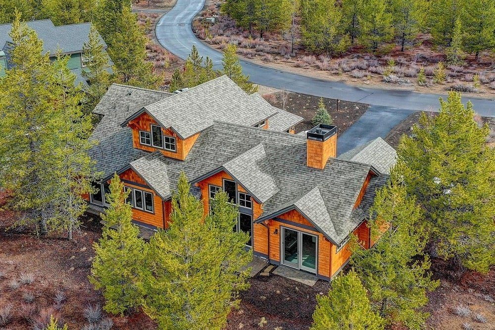This is an aerial view of the house with asphalt driveway and landscaping of tall pine trees that bring color to the wooden exterior walls and gray roof of the house.