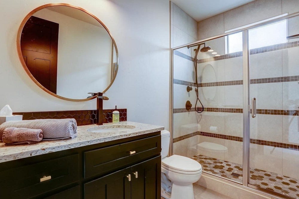 This is a simple primary bathroom with a dark wooden vanity topped with a large circular mirror next to the toilet and the glass-enclosed shower area on the far wall with a window above.