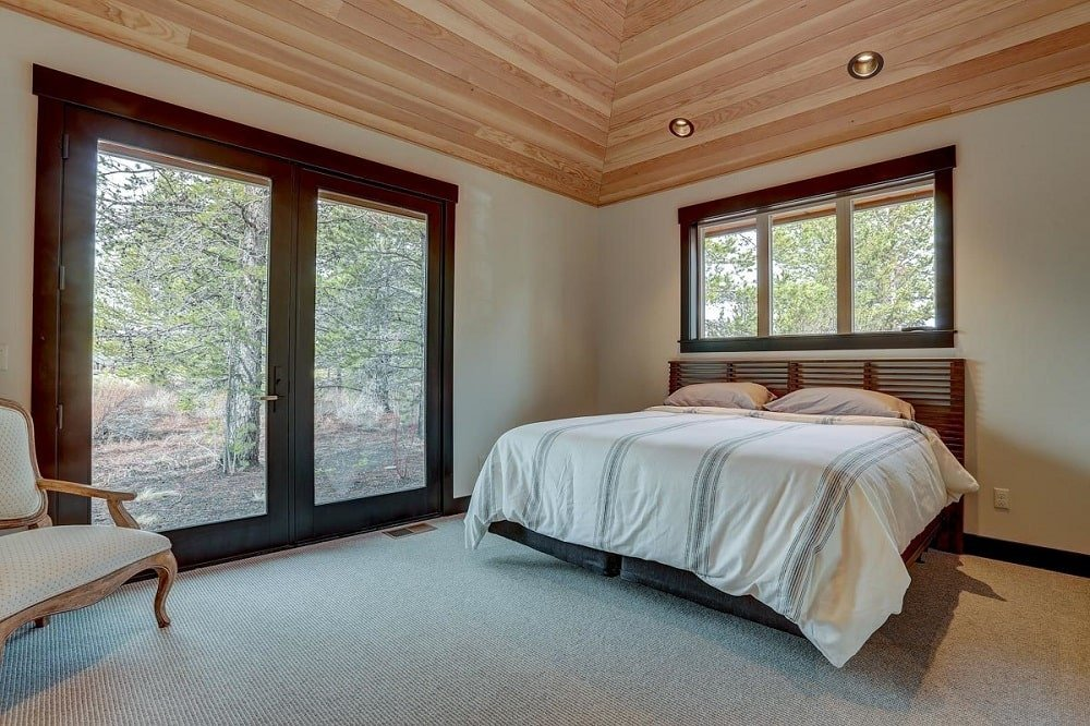 The primary bedroom has a simple traditional bed paired with a large window and glass doors that stand out against the white walls with their dark wooden frames. These are then topped with a wooden shiplap arched ceiling.