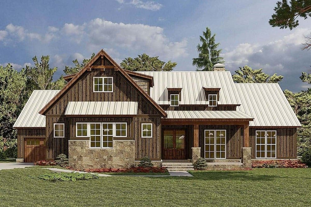 This is a unique mountain farmhouse-style home with dark wooden brown exterior walls complemented by the stone accents and the dormer windows above that match the multiple windows of the house.