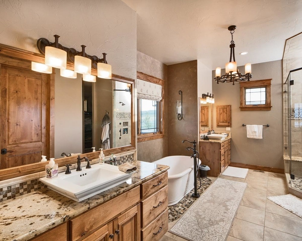 This is the primary bathroom with a large freestanding bathtub in the middle of the two vanitues with wooden drawers and wall-mounted lamps that match the chandelier hanging from the ceiling.