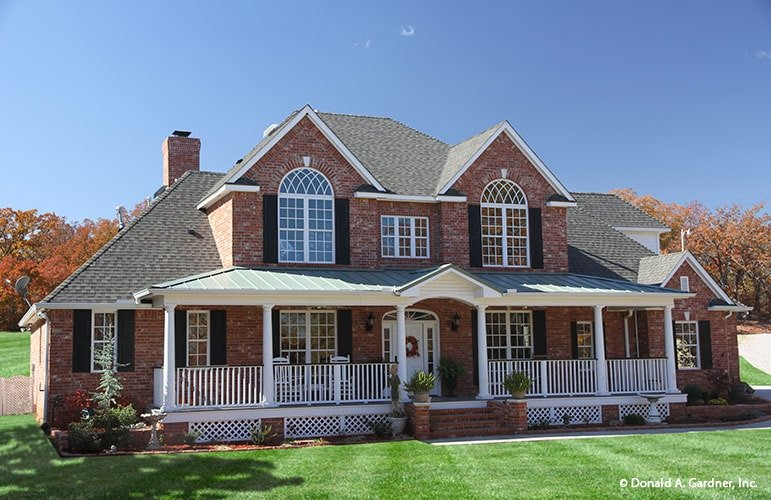 This is a front view of a two-story peppermill farmhouse-style home with brick walls and large arched windows along with a front porch.