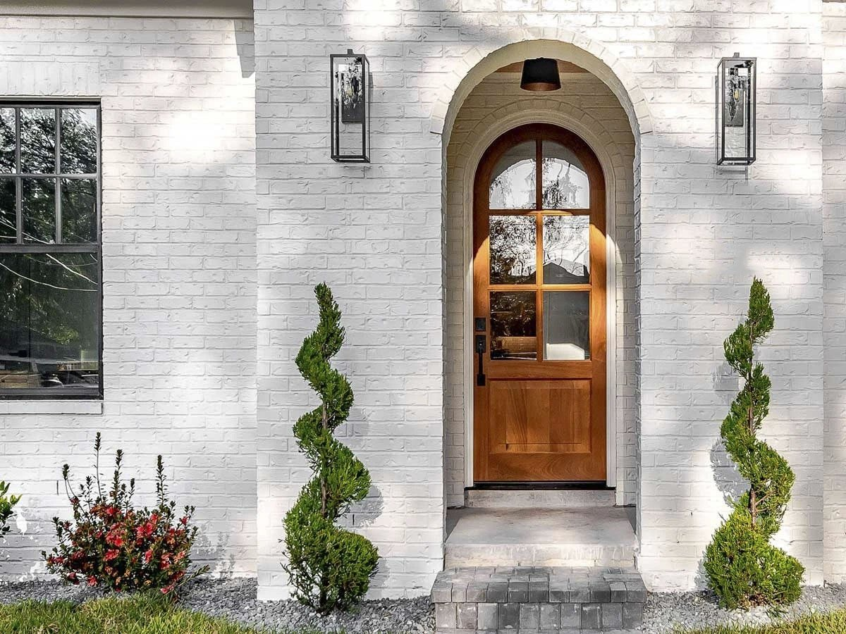 Home entry with decorative arches and a glazed front door.