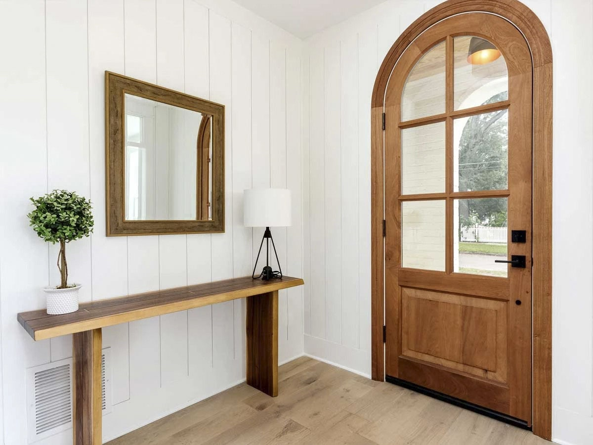 The foyer has a wooden console table and a matching mirror fixed against the beadboard wall.