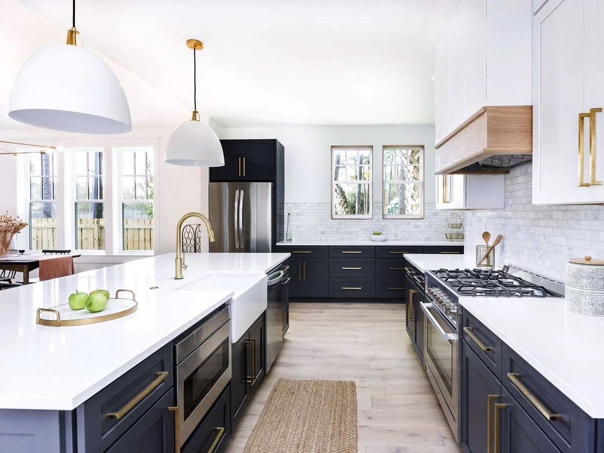 The kitchen has contrasting white and black cabinetry accentuated with brass fixtures.