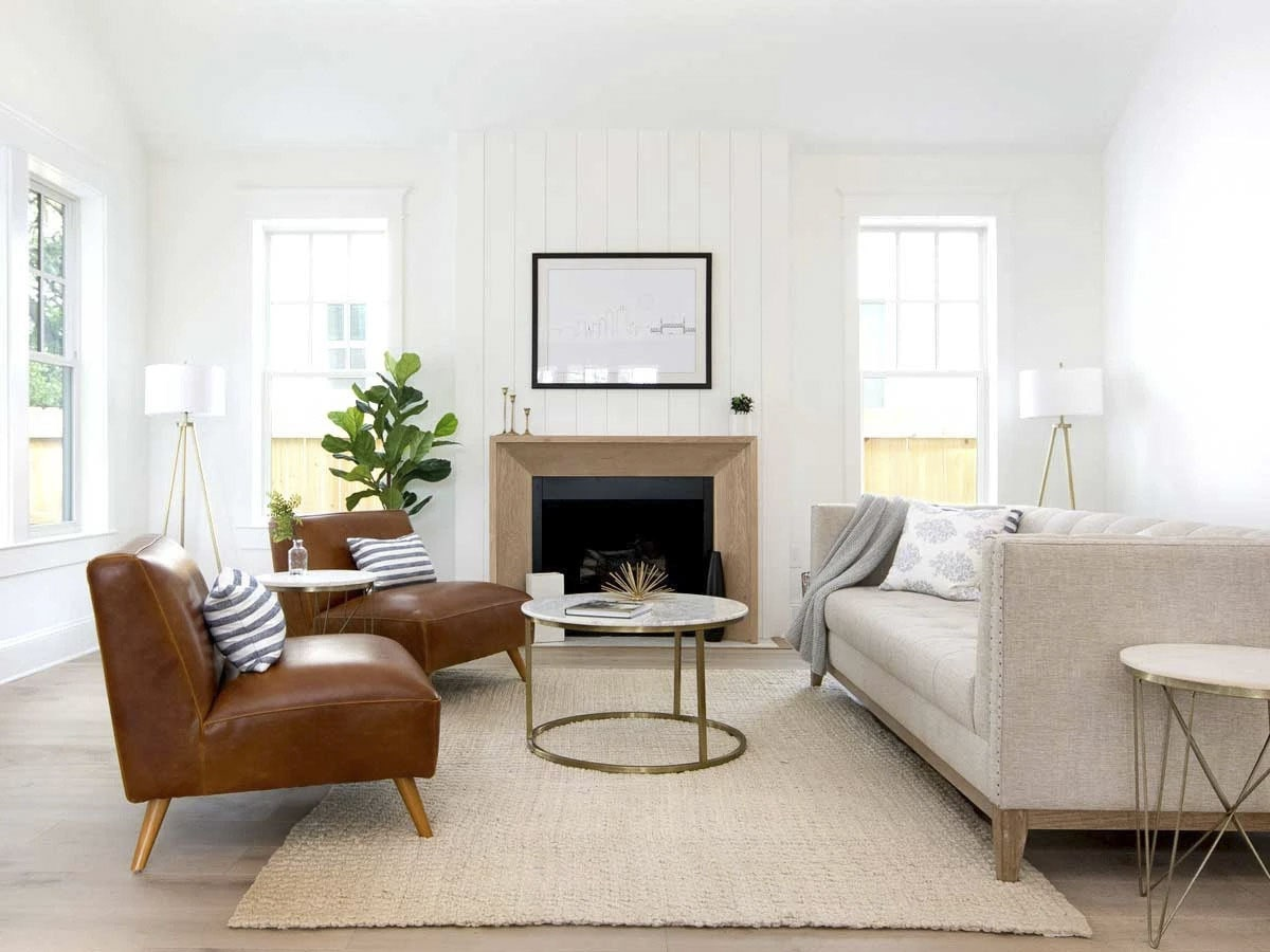 Living room with a tufted sofa, leather chairs, round coffee table, and a cozy fireplace.