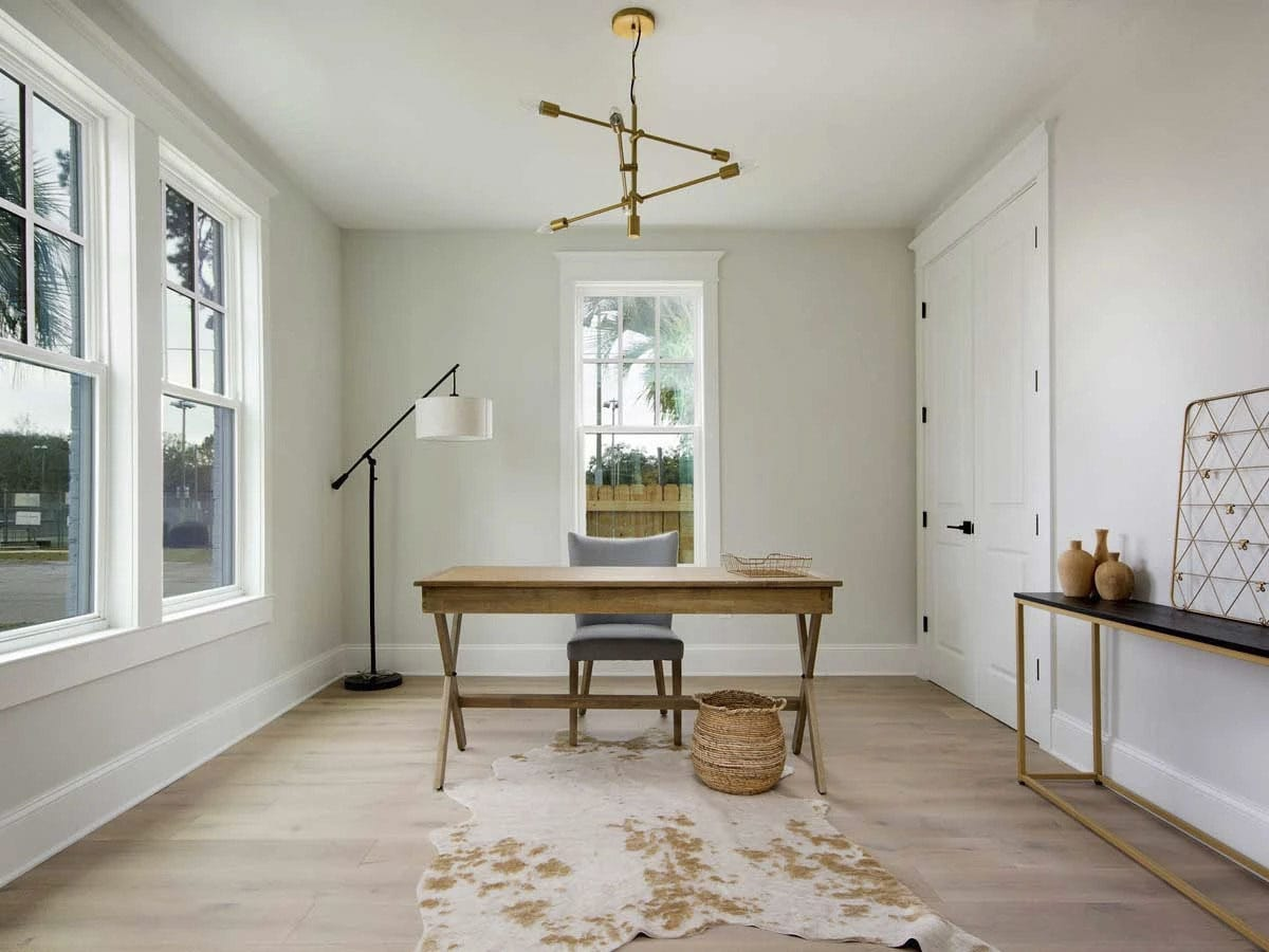 Home office with neutral walls and light hardwood flooring topped by a cowhide rug.
